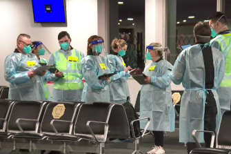 Authorised officers check the identification of passengers arriving atMelbourne Airport on Thursday.