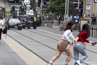 Pedestrians flee as a car is driven along Bourke Street Mall on January 28.