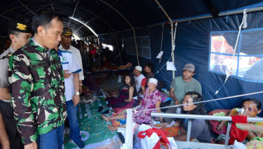 Indonesian President Joko Widodo talks with tsunami survivors in a temporary shelter in Palu on Sunday.