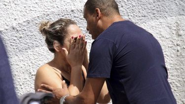 A man comforts a woman at the Raul Brasil State School in Suzano, Brazil, following the shooting.