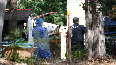 A police forensic officer (left) tends to the scene of the suspected double murder of Frank and Loris Puglia in Joyner in Brisbane's north, on Monday.