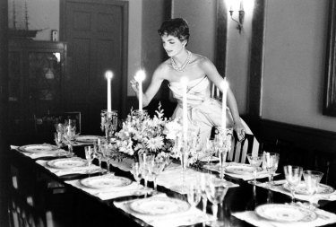 Newlywed Jackie Kennedy, dressed to the nines, lights candles for a dinner party.