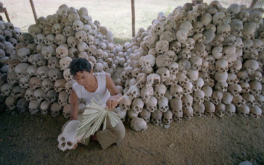 A man cleans a skull near a mass grave at the Chaung Ek torture camp run by the Khmer Rouge, in this undated photo.