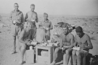 Lieutenant John Rosel (seated left) and the Rats of 2/24 Battalion snatch time for lunch outside Tobruk.