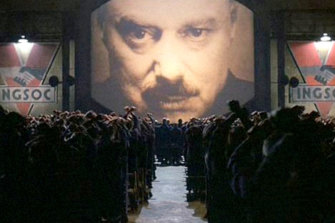 A still from the movie 1984, showing Big Brother and the masses.