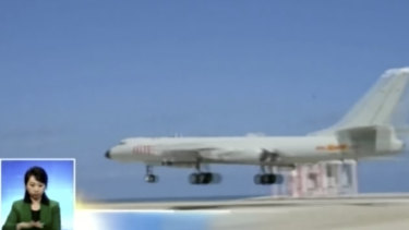 A Chinese H-6K bomber flying along a runway in the South China Sea.