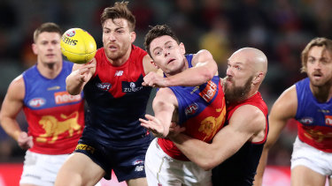 Lachie Neale tackled by Max Gawn.