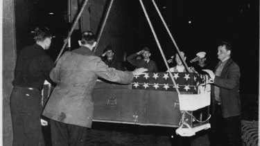 A casket containing the body of an unidentified American soldier, killed on the Korean battlefields, is lowered by longshoremen from the USS General Randall onto US soil on March 22, 1951.