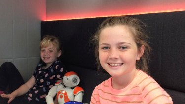 Ella and older sister Ava, 11,  with two of the smaller robots at the centre.