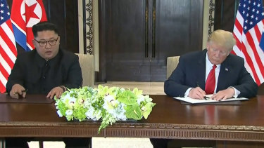 Donald Trump and Kim Jong-un sign statements after their Singapore meeting.