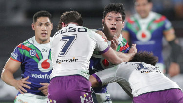 Wrapped up: Issac Luke of the Warriors is tackled by Brodie Croft and Felise Kaufusi.