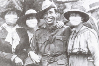 A returned soldier poses with women in anti-flu masks, 1919.