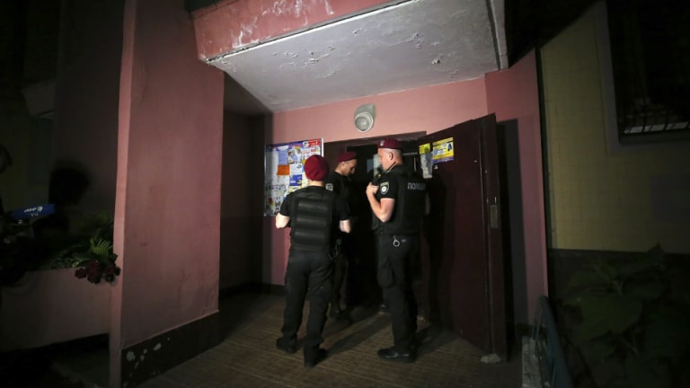 Police guard the front door of the Kiev apartment block where Arkady Babchenko reportedly died.