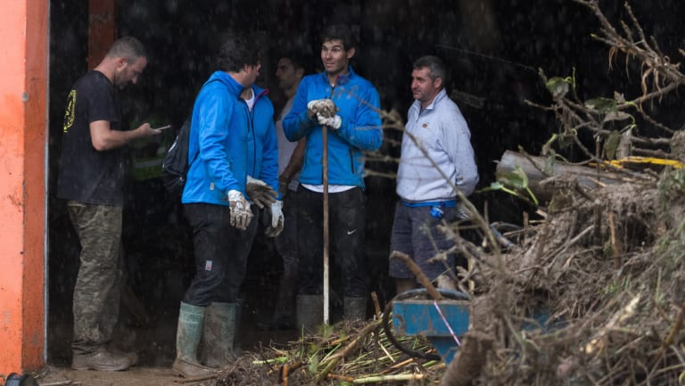 Rafael Nadal (centre) works with residents to clear from homes after flooding in Majorca.