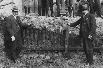 Men pose in front of the picket fence unearthed in the early 1920s during excavation work for the Capitol Theatre on Swanston Street.