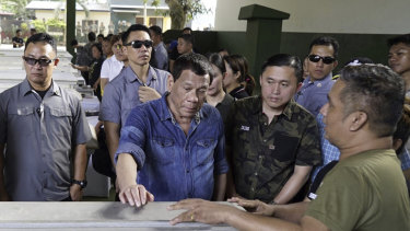 Philippine President Rodrigo Duterte, centre, touches one of the coffinss of victims of last Sunday's bombings of a Roman Catholic Cathedral on Jolo.