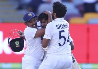 Indian players celebrate after defeating Australia by three wickets on the final day of the fourth cricket test at the Gabba.