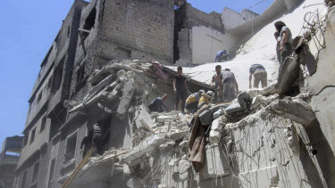 White Helmets inspect a damaged building after an air strike by Syrian government forces, in the town of Ariha, in the north-western province of Idlib.
