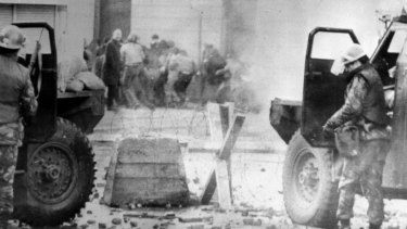 Soldiers take cover behind their armoured cars in Northern Ireland. in January 1972.