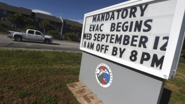A sign warns residents about the mandatory evacuation in front of Wrightsville Beach Park in Wrightsville Beach, NC.