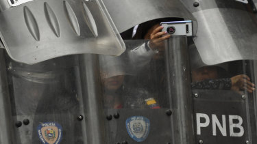 A riot police officer takes a photo while blocking an opposition march in Caracas on Tuesday.