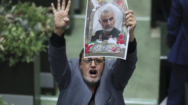 "Iranian lawmaker Mohammad Javad Abtahi holds a poster of General Qassem Soleimani as he encourages his colleagues to vote for a bill that declares the  US military's command at the Pentagon and those acting on its behalf ""terrorists""."