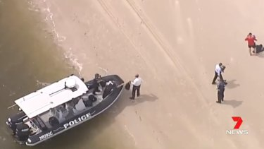Police arrive at the beach on the northern tip of Bribie Island where the bodies were found.