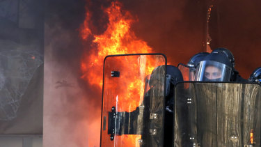 Riot police officers stand in front a burning building during a yellow vests demonstration on Saturday in Paris.