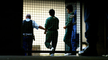 Pong Su crew members being escorted out of Sydney Central Local Court in 2003