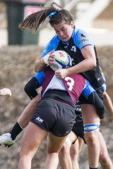 UC's Samantha Wood gets tackled by Queenslands Pleuni Kievit.