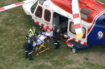 An injured man is loaded onto an air ambulance on Friday afternoon.