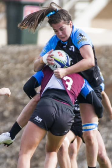 UC's Samantha Wood gets tackled by Queenslands Pleuni Kievit.