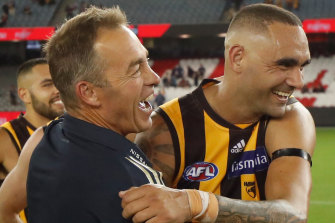 Hawks coach Alastair Clarkson, left, celebrates after his side beat the Bombers on Saturday.