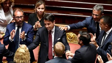 Italian Prime Minister Giuseppe Conte, centre, is congratulated at the end of his resignation address to the Senate in Rome.