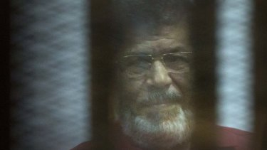 Former Egyptian president Mohammed Morsi, in a red jumpsuit reserved for those sentenced to death, sits in a defendant's cage in court in 2016.