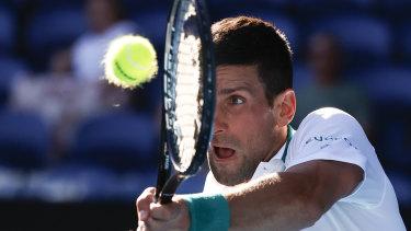 Novak Djokovic makes a backhand return to Frances Tiafoe.