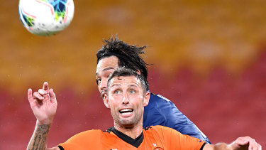 Scott McDonald of the Roar and Eunsun Kim of the Mariners challenge for the ball.