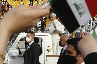 Pope Francis waves as he arrives for an open air Mass at a stadium in Erbil, Iraq.
