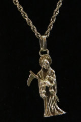 """A necklace made of white gold with a pendant in the image of """"Holy Death"""", which was on display but removed from the auction due to the image it represents."""