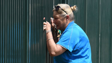 A woman speaks to someone through the fence as NSW Police and NSW Ambulance attend Plumpton High School.