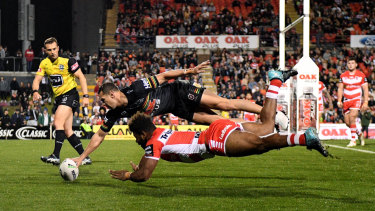 Brent Naden outleaps Mikaele Ravalawa to touch down for the Panthers.