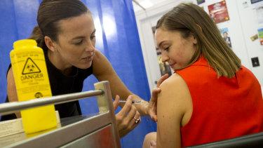 Pharmacist Jane Mitchell administers the flu shot.