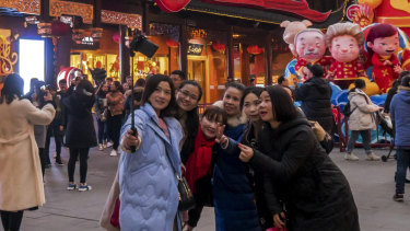 Women take a selfie at the Yu Garden decorated with pig statues for Lunar New Year in Shanghai on Saturday. The latest economic figures show China's middle class is rapidly expanding.