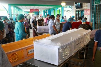People wait while caskets with the bodies of COVID patients are queued outside a crematorium at the Yay Way cemetery in Yangon, Myanmar.