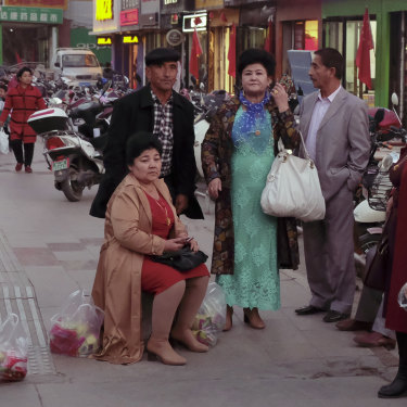 A group of older Turpan locals wait, in western dress, in front of a market.