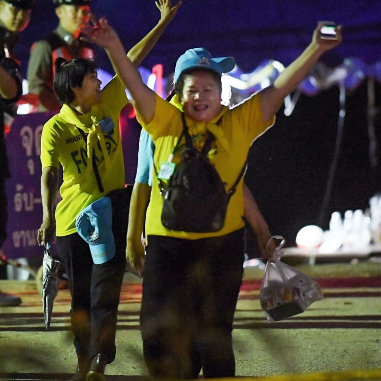 """Thai volunteers cheer and yell """"hooray"""" as they return from Tham Luang cave after the group was rescued."""