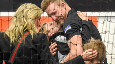 Collingwood coach Nathan Buckley being comforted by his family after the Pies loss.