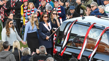 Danny Frawley's wife and daughters walk behind his hearse at Moorabbin Oval.