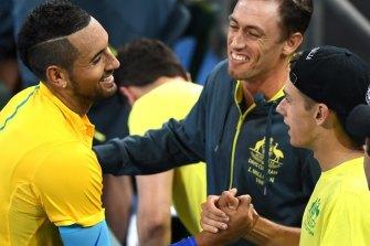 Supportive: Davis Cup teammates John Millman and Alex de Minaur (cap) congratulate Nick Kyrgios earlier this year.