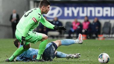 Sliding doors: Sydney FC striker Adam Le Fondre slides in on Perth goalkeeper Liam Reddy to score last night.